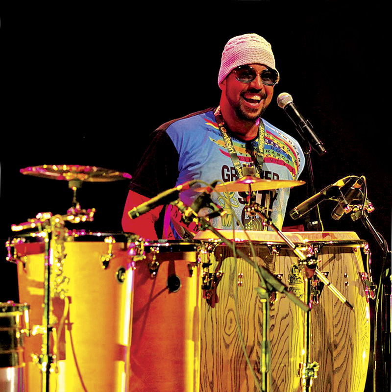 Dressed colorfully and wearing shades, Marcus Santos stands behind an array of Brazilian hand drums