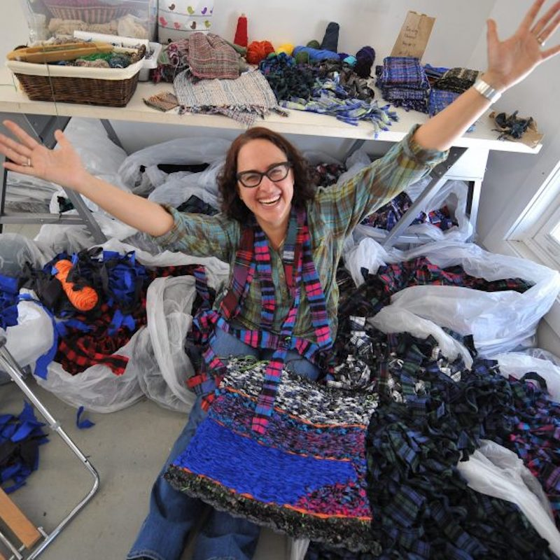 YAMA fiber arts teaching artist Stacey Piwinski surrounded by colorful materials. Photo Credit: Viet Van Tran
